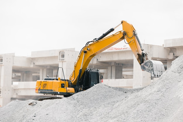 Escavadeira trabalhando na rocha do canteiro de obras, movendo-se para a construção de pedágio