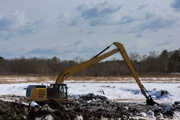Escavadeiras de movimentação de terra com equipamentos pesados durante a escavação da retroescavadeira do canteiro de obras para a colocação de tubos de esgoto nas obras