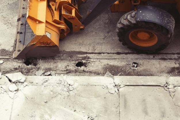 Escavador amarelo e asfalto rachado