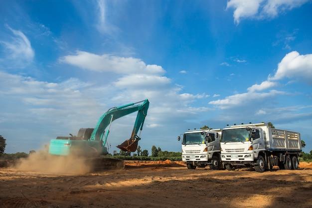 Escavador do local de construção, máquina escavadora e caminhão de descarregador. maquinaria industrial no local de edifício
