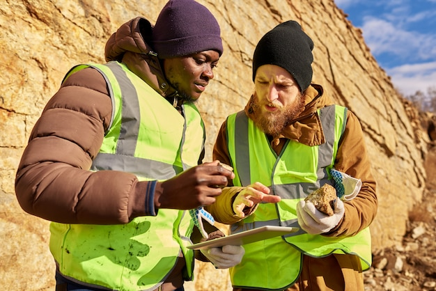 Escavadores que inspecionam o local de trabalho em busca de minerais