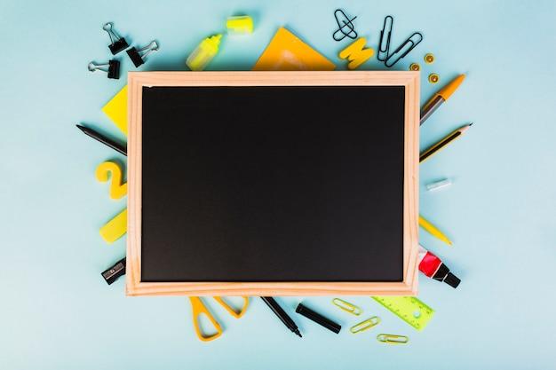 Escola colorida e material de escritório em torno de lousa