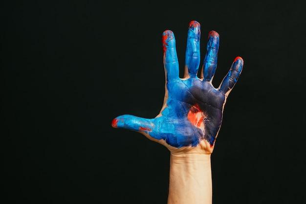 Escola de arte moderna. classe mestre. criatividade e inspiração. closeup de mão masculina suja de tinta. espaço vazio de fundo escuro.