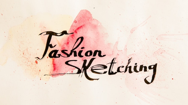Escola de artes. desenho de moda. letras cursivas pretas criativas em papel envelhecido manchado de tinta vermelha.