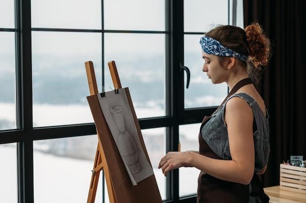 Escola de artes. vista lateral de uma jovem desenhando um vaso