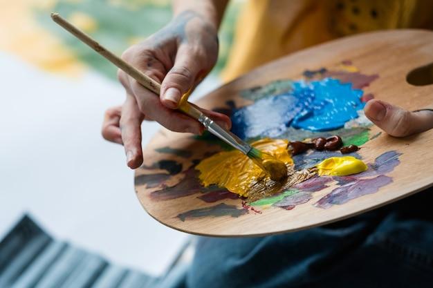 Escola de belas artes. closeup de mãos de artista segurando uma paleta de madeira, misturando tinta acrílica com pincel.
