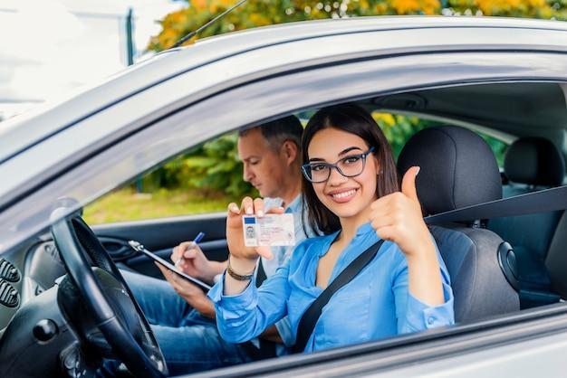 Escola de condução. a mulher nova bonita passou com sucesso o teste da escola de condução. ela está olhando