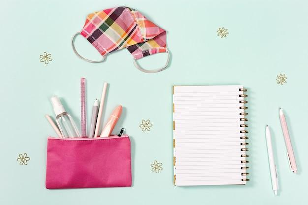 Escola de mesa de trabalho de novo conceito normal com material de escritório para meninas e equipamentos de proteção individual.
