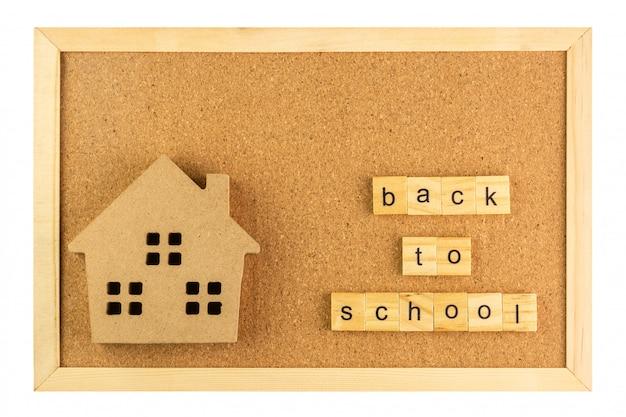 Escola de modelo pequeno e volta à palavra escola na placa de cortiça no frame de madeira, isolado no fundo branco