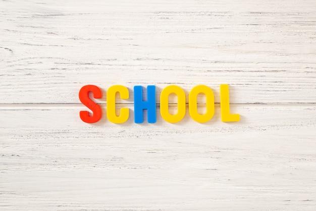 Escola de palavras de madeira colorida em um fundo branco de madeira