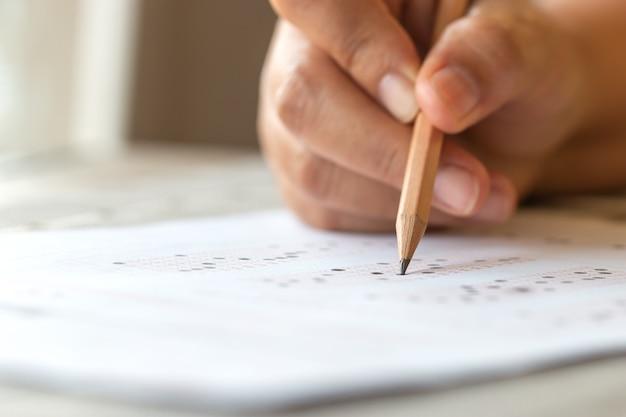 Escola de teste de exame ou conceito de universidade: aluno de mão segurando lápis escrevendo resposta padronizada forma de papel carbono com folha de respostas cinza preto borbulhando de pergunta na avaliação do exame.