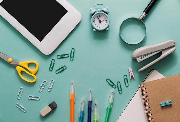 Escola definida com canetas de notebooks laptop tesoura grampeador lupa sobre um fundo azul voltar para ...