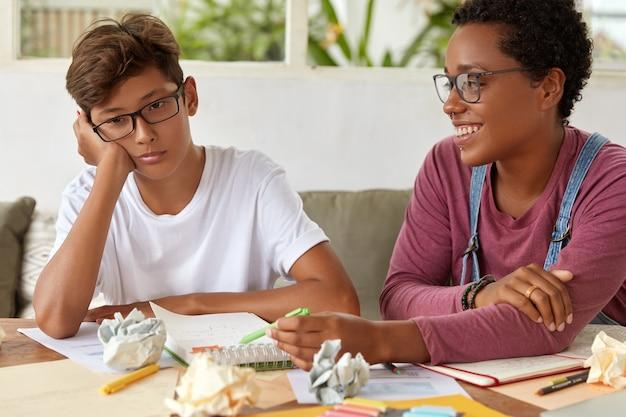 Escola e conceito de educação. professora experiente e satisfeita ajuda o jovem a acompanhar o grupo, explica a regra gramatical, faz anotações no bloco de notas. adolescente sente apatia porque não quer estudar