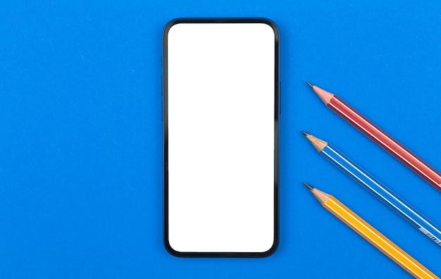 Escola e estudo de maquete de smartphone, mesa de escritório azul com lápis, foto da vista superior