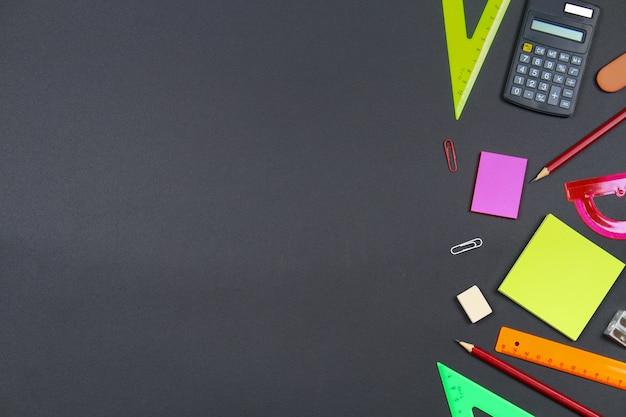 Escola e material de escritório no fundo do quadro-negro. vista superior com espaço de cópia.