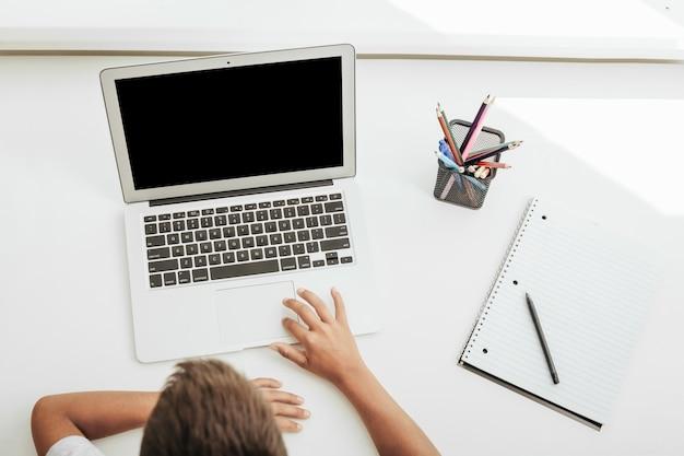 Escola em casa através do ensino doméstico online. a criança está sentada no computador