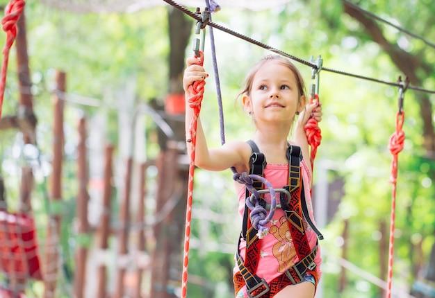 Escola feliz mulher desfrutando de atividade em um parque de aventura escalada num dia de verão,