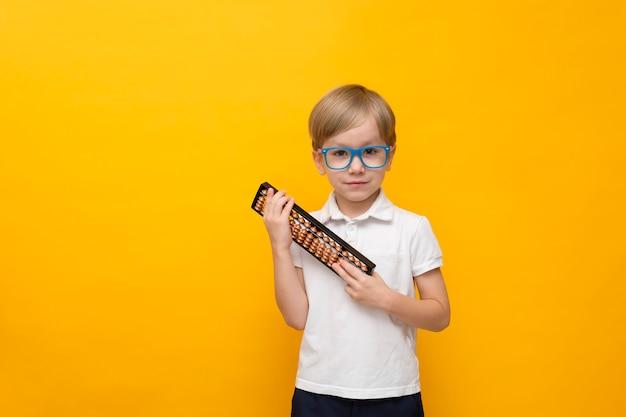 Escola menino bonitinho de óculos, segurando o ábaco amarelo