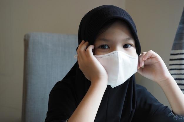 Escola muçulmana criança auto-isolamento, ficar em casa com máscara