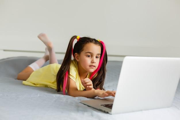 Escola online legal. garoto estudando on-line em casa usando um laptop. menina jovem alegre usando computador portátil estudando através do sistema de ensino on-line. aprendizagem a distância ou remota