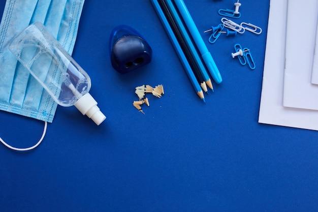Escola plana leiga após a pandemia de coronavírus, volta às aulas em uma nova realidade, material escolar, máscara protetora e anti-séptico em um fundo azul, espaço para texto.