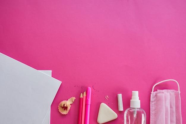 Escola plana leiga após a pandemia de coronavírus, volta às aulas em uma nova realidade, material escolar, máscara protetora e anti-séptico em um fundo rosa, espaço para texto.