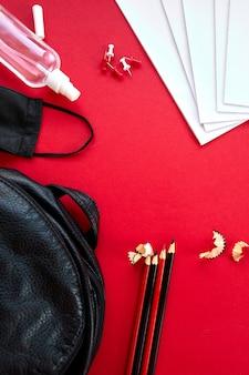 Escola plana leiga após a pandemia de coronavírus, volta às aulas em uma nova realidade, material escolar, máscara protetora e anti-séptico em um fundo vermelho Foto Premium