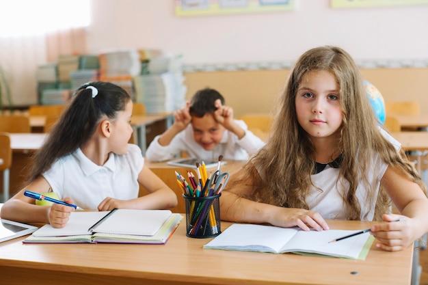 Escolas sentadas em mesas na sala de aula