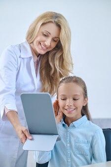 Escolha certa. menina feliz em idade escolar em idade escolar experimentando aparelho auditivo e uma simpática médica segurando um espelho
