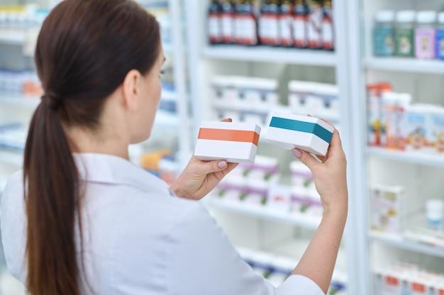 Escolha certa. vista traseira de uma mulher de cabelos compridos vestindo jaleco branco examinando dois pacotes de medicamentos em frente às prateleiras da farmácia