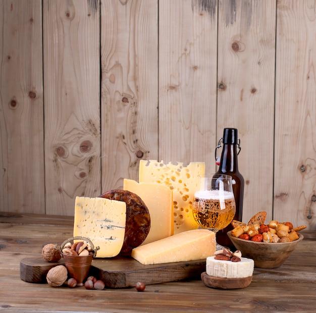 Escolha clássica de queijo diferente, em uma prancha de madeira velha e nozes. queijo diferente em uma prancha de madeira velha. queijo holandês e cerveja