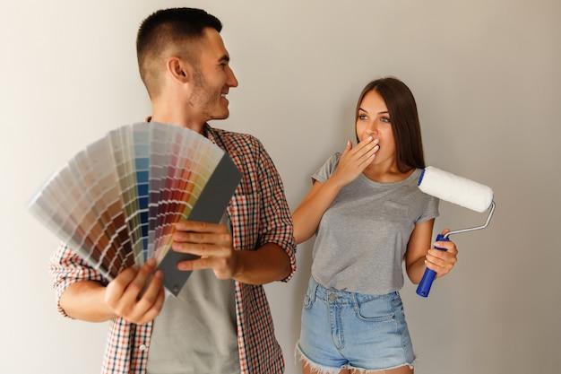 Escolha da cor para pintar a parede. casal com paleta de cores e rolo de pintura