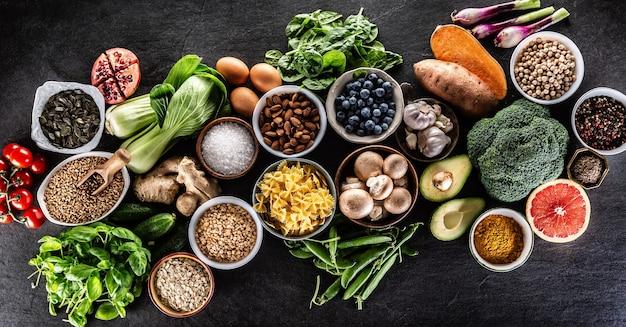 Escolha de alimentos frescos e alimentação saudável: vegetais, frutas, legumes e cereais em uma mesa de concreto - vista superior.