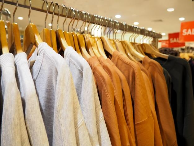 Escolha de roupas da moda de cores diferentes em cabides de madeira