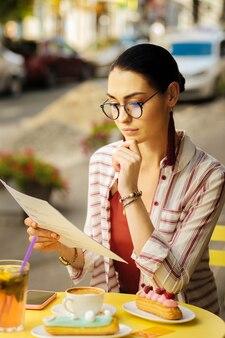 Escolha difícil. calma atenta jovem olhando pensativamente o cardápio enquanto se senta à mesa coberta de saborosas sobremesas