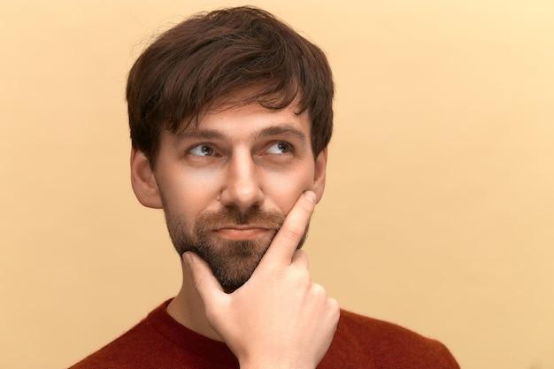 Escolha difícil. foto de jovem com barba, vestindo um suéter, segura o queixo, franze os lábios com expressões sem noção, dúvidas sobre algo, posando contra uma parede bege