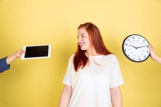 Escolha difícil. retrato de mulher jovem caucasiana em fundo amarelo do estúdio, muitas tarefas. como gerenciar o tempo certo. conceito de trabalho de escritório, negócios, finanças, freelance, autogestão, planejamento.