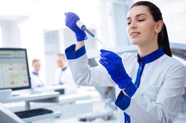 Escolha perfeita. inspirou a linda estagiária segurando o frasco olhando para ele com atenção enquanto posava no laboratório