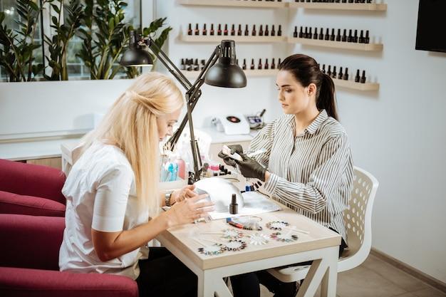 Escolhendo a cor. mulher loira atraente e bem-sucedida escolhendo a cor de goma laca para a manicure