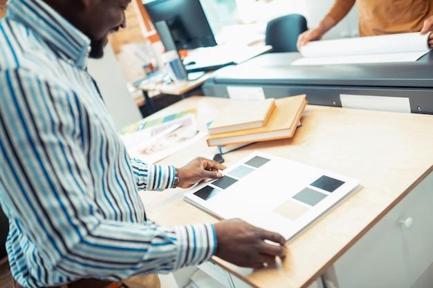 Escolhendo a cor. vista superior de um homem de pele escura vestindo uma camisa listrada escolhendo a cor para a capa do livro