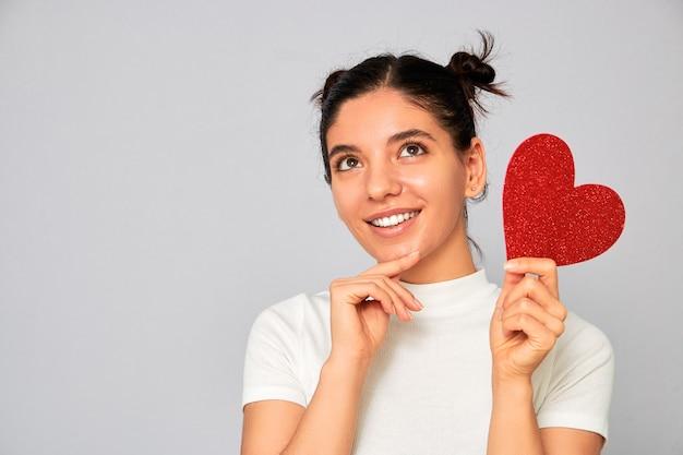 Escolhendo a variante certa. retrato de mulher segurando um coração vermelho cintilante dos namorados pensando enquanto sorri