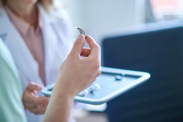 Escolhendo aparelho auditivo. mão segurando um aparelho auditivo elegante e elegante na consulta com o otorrinolaringologista, sem rosto