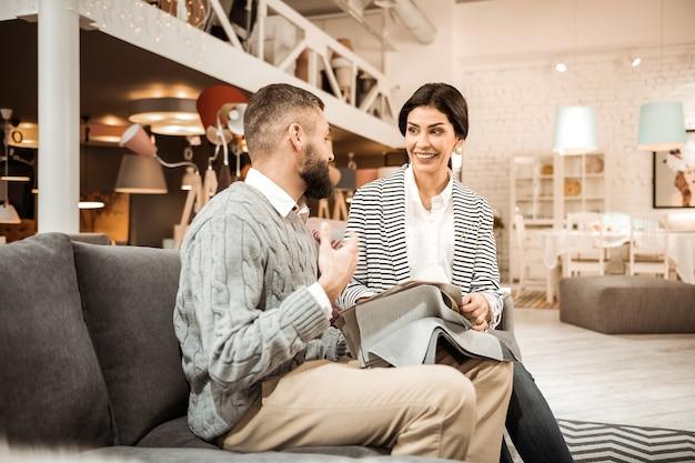 Escolhendo detalhes. casal radiante e positivo, passando um tempo em uma loja de móveis e discutindo vários materiais