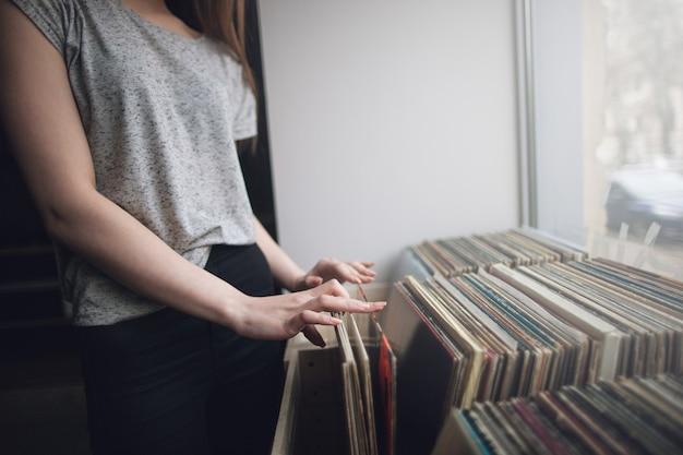 Escolhendo discos de vinil retrô. fundo de música. mulher irreconhecível em loja musical, estilo hipster da velha escola