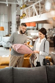 Escolhendo fronhas. casal alegre e positivo parado no meio de uma loja de móveis aplicando amostras de tecido para uma visão melhor