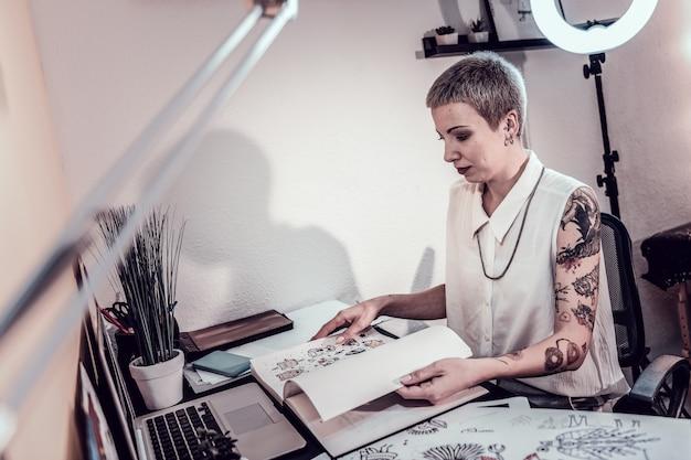 Escolhendo novos esboços. artista extraordinariamente ocupada folheando álbum com pinturas em seu gabinete