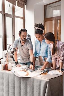 Escolhendo o material perfeito. grupo de três pessoas no estúdio de design. homem e duas mulheres estão tomando decisões