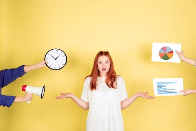 Escolhendo. retrato de mulher jovem caucasiana em fundo amarelo do estúdio, muitas tarefas. como gerenciar o tempo certo. conceito de trabalho de escritório, negócios, finanças, freelance, autogestão, planejamento.