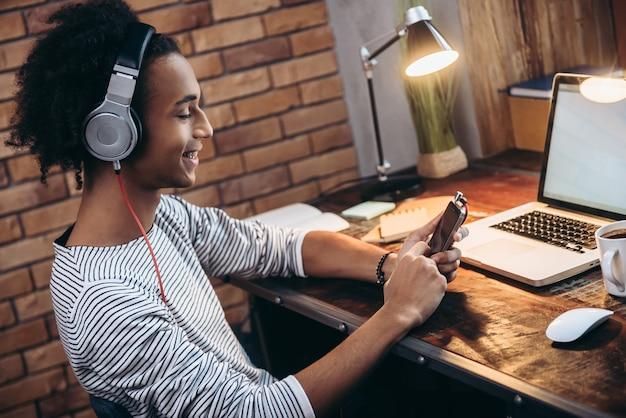 Escolhendo uma lista de reprodução perfeita. vista lateral de um jovem africano alegre usando fones de ouvido e segurando um telefone inteligente com um sorriso enquanto está sentado em seu local de trabalho