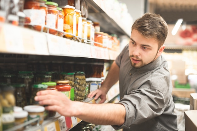 Escolher e comprar tomates em lata no supermercado.